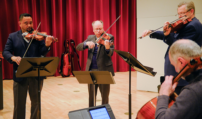 Four people standing, playing in a string quartet
