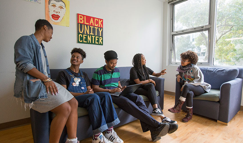 Four students sit next to a professor on a couch under a sign that reads Black Unity Center.