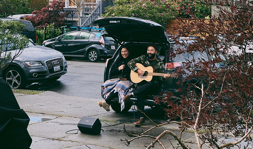 Duo sits in the back of their station wagon and performs music