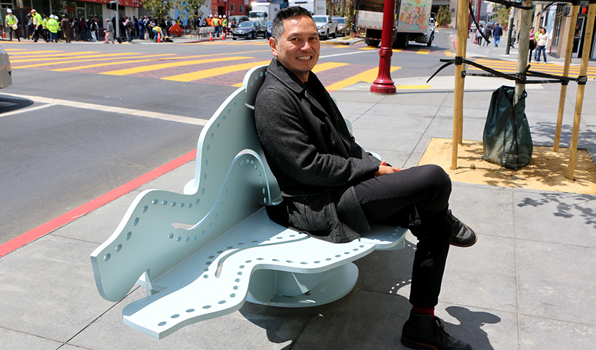 Artist Michael Arcega sits on a cloud-shaped bench that he created.