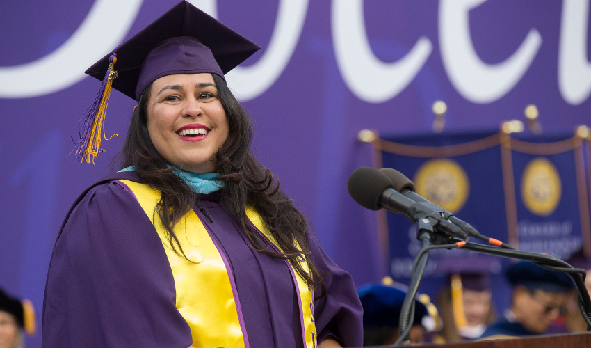 Woman in purple and yellow graduation regalia, standing at podium and smiling
