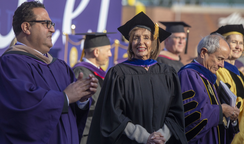 Nancy Pelosi faces the camera dressed in a black robe and cap, surrounded by others in purple.