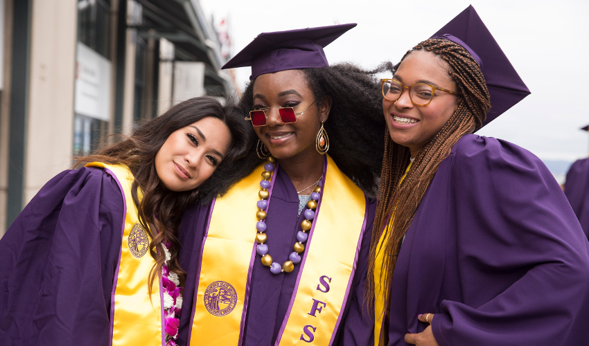 Three students in purple graduation robes and caps smile at the camera