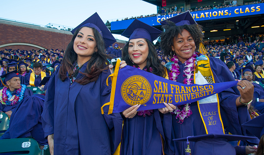 Three graduates holds a SF State pennant at Comemncement