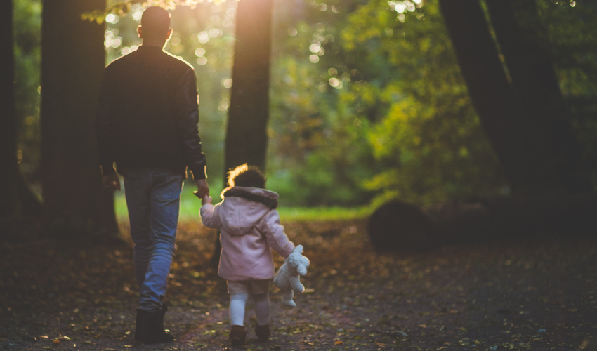 Man and child, holding hands, facing away from the camera and walking through woods.