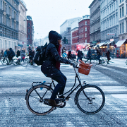 Person on bicycle crosses a snowy intersection in Copenhagen