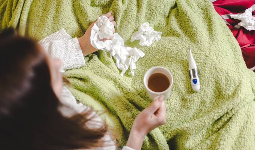Woman in blanket with tissues, mug of tea and thermometer