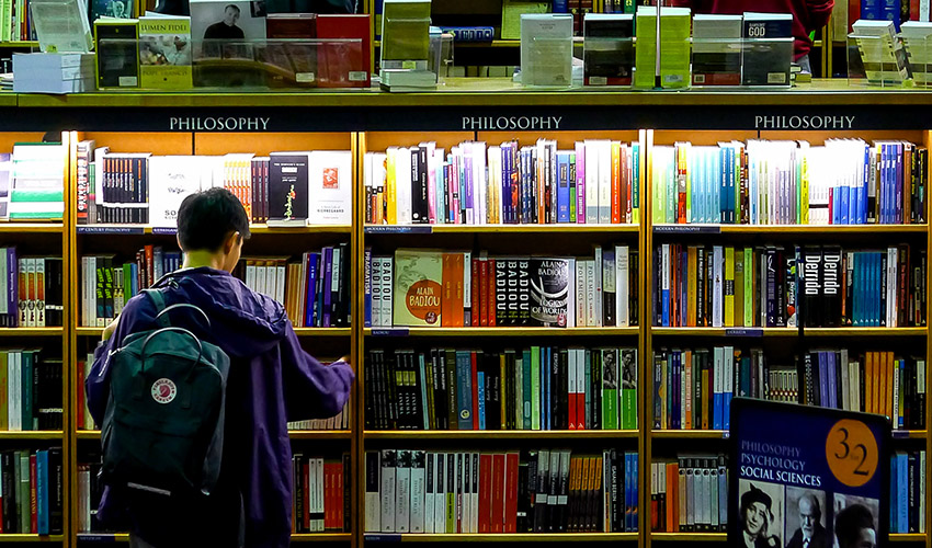 A student ponders a shelf full of textbooks.