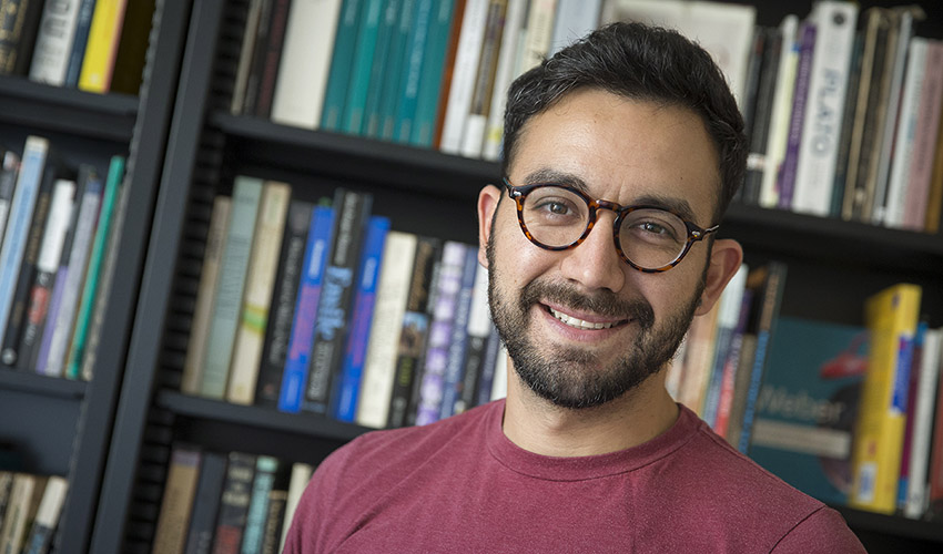 David Peña-Guzmán stands in front of a bookshelf in his office.