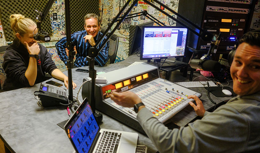 A student and Dennis O'Donnell speak into microphones in a sound booth at SF State