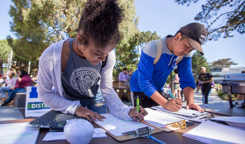 SF State students registering to vote at a table in the quad.
