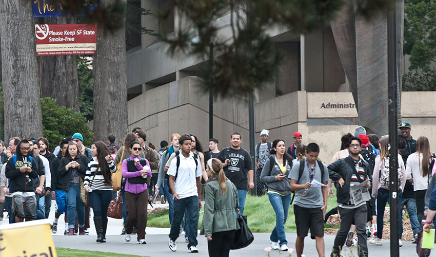 Several dozen SF State students walk through the quad on a sunny day.