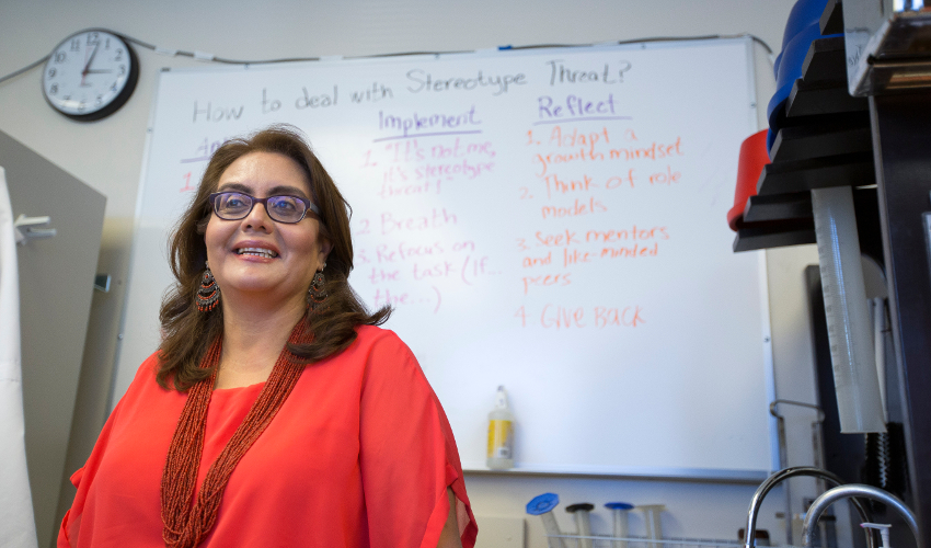 Leticia Márquez-Magaña, dressed in red, stands in front of a whiteboard with writing on it