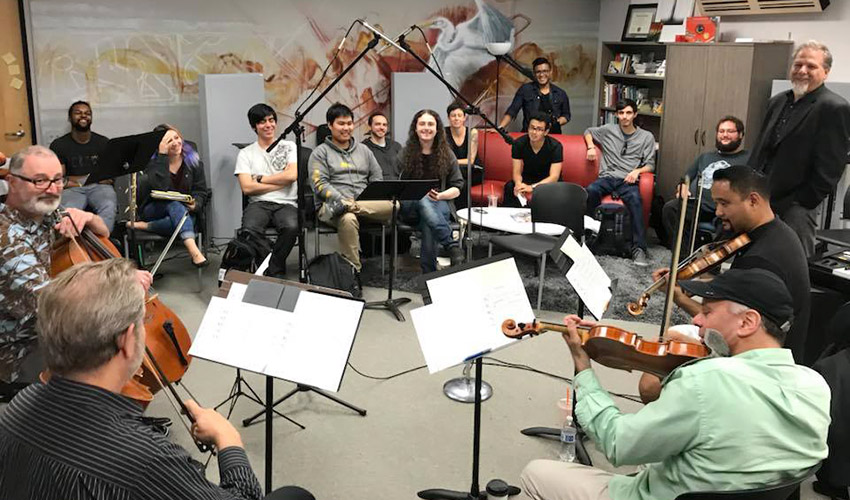 String musicians play their instruments as students watch in a music studio.