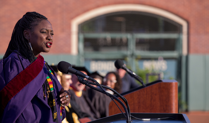Alicia Garza, dressed in commencement regalia, at podium