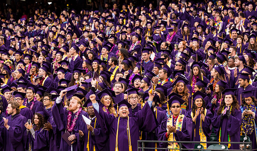 A crowd of students dressed in their graduation robes stand in the stadium