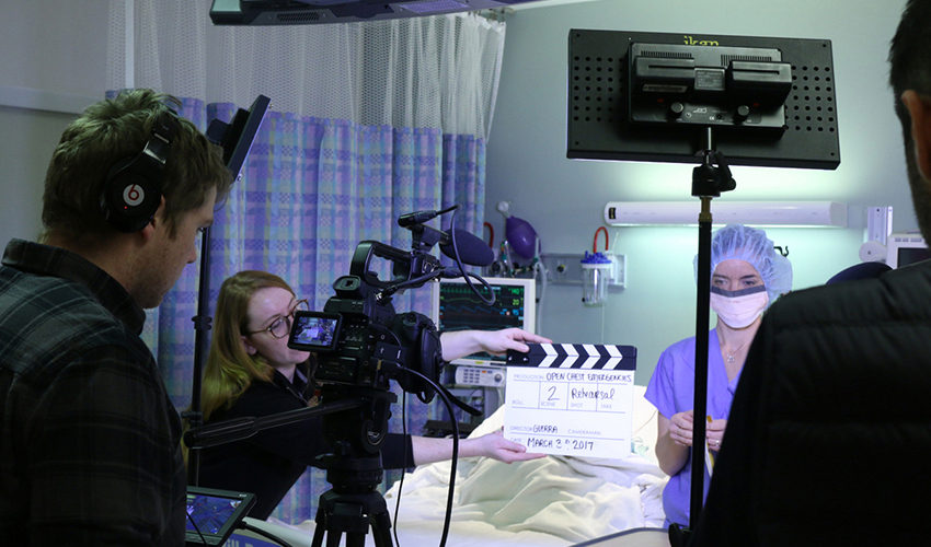 Photo of students and Professor Oscar Guerra shooting video in an operating room
