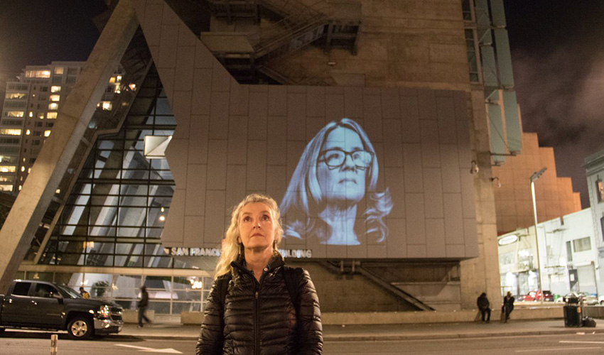 Rebecca Solnit stands in front of a building in downtown San Francisco