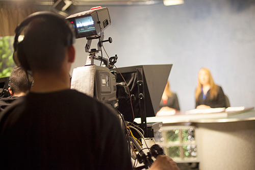 View over camera operator's shoulder toward camera and TV studio newscasters