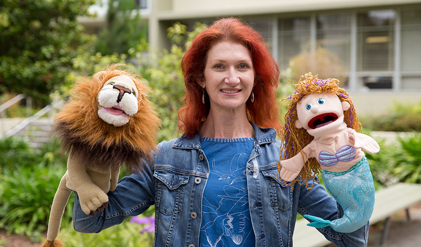 Jenny Debevec holds a lion puppet and a mermaid puppet on her hands to demonstrate one of her improv techniques.