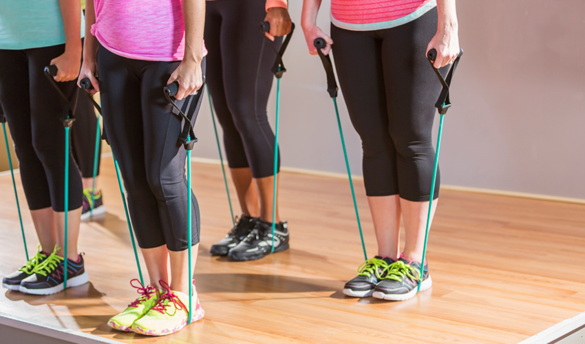 A group of women conduct resistance band exercises in a gym.