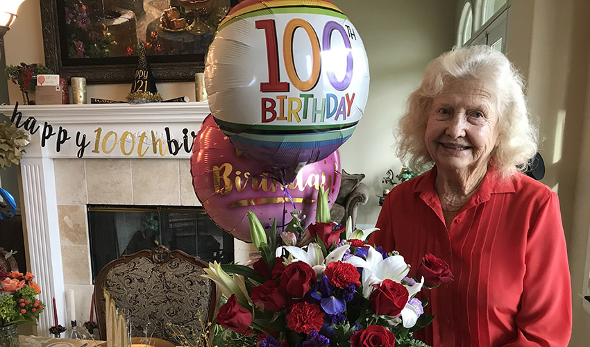 Lucille Wendling poses with balloons and flowers for her 100th birthday celebration