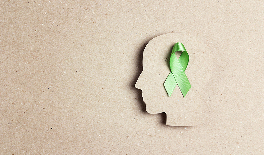 Overhead view of a green ribbon placed on top of a paper cutout of a head shape.