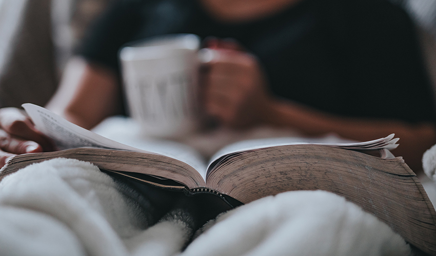 Person reading a book while holding a cup