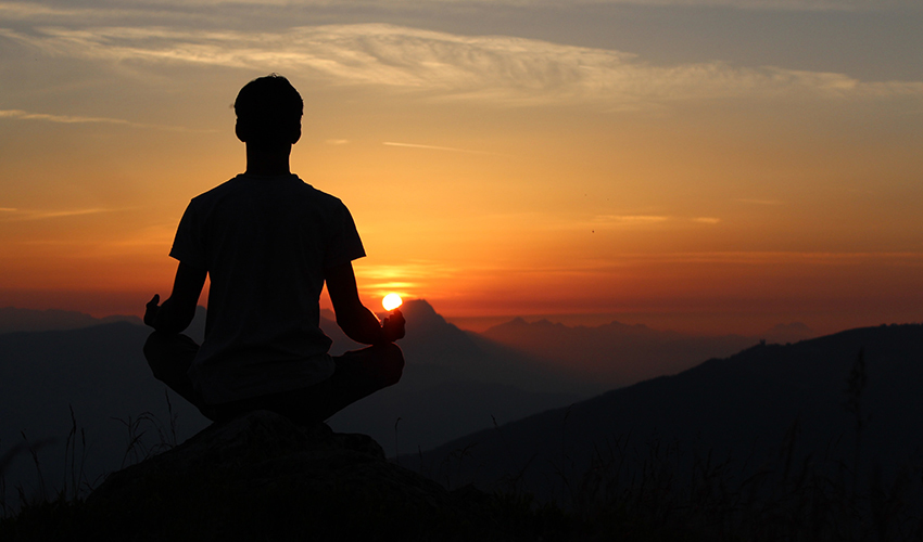 Silhouette of a person sitting – assumably meditating — while looking at a fading sun on the horizon.