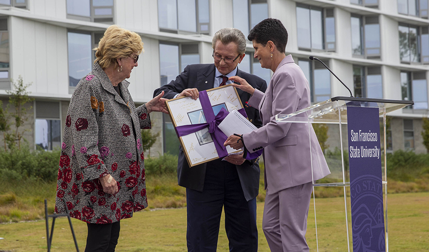 Woman in lavender suit presenting a large framed photo to two people