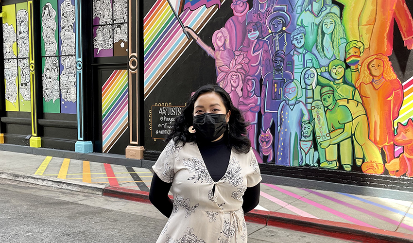 Artist poses in front of the rainbow-color mural she painted in San Jose.