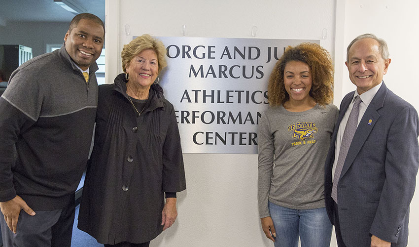 "Athletic Director Charles Guthrie, alum Judy Marcus, track and field athlete Tamiyah Thomas and President Les Wong in front of a sign reading ""George and Judy Marcus Athletic Performance Center."""