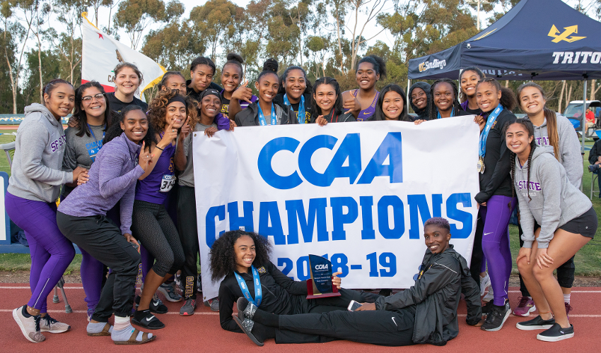 "Students at a running track hold up a sign reading ""CCAA Champions 2018-19"""