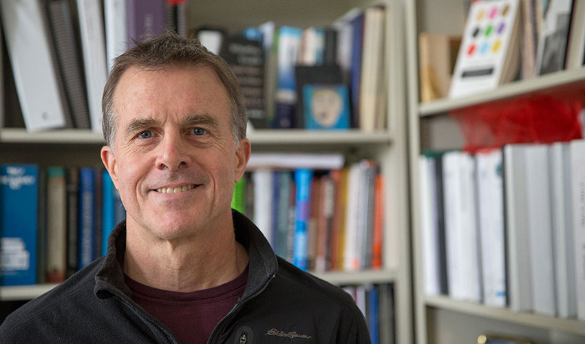 SF State Professor of Health Education Adam Burke stands in front of a bookshelf in an office at the College of Health and Social Sciences.