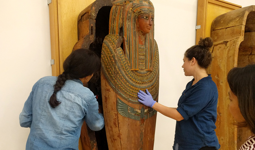 Photo of three people handling a sarcophagus