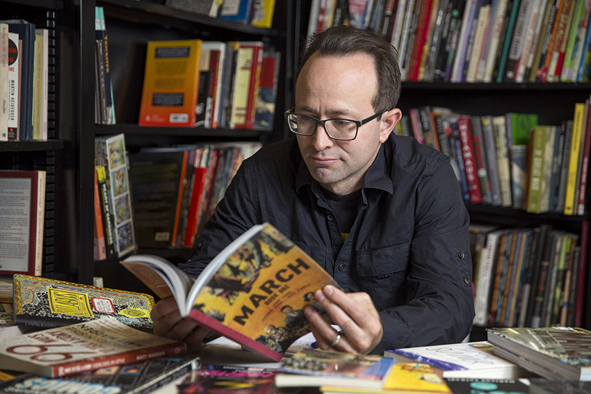 SF State Professor of Humanities and Liberal Studies Nick Sousanis reads a graphic novel in his classroom.