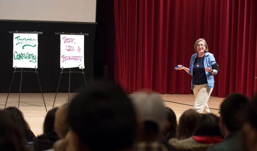Instructor stands in the front of a large lecture hall