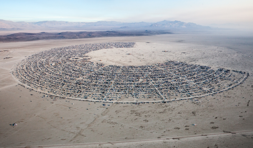 Aerial photo of a large arc of small structures in the desert with mountains in the background