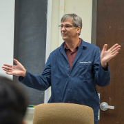 A man in a blue lab coat lectures students in a classroom