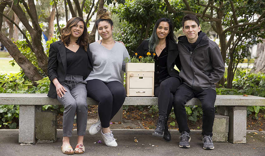 Three female students and one male student posing with their compost machine