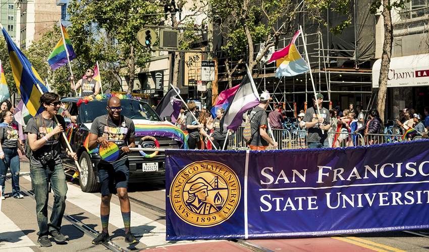 Marchers hold the an SF State banner and march in street