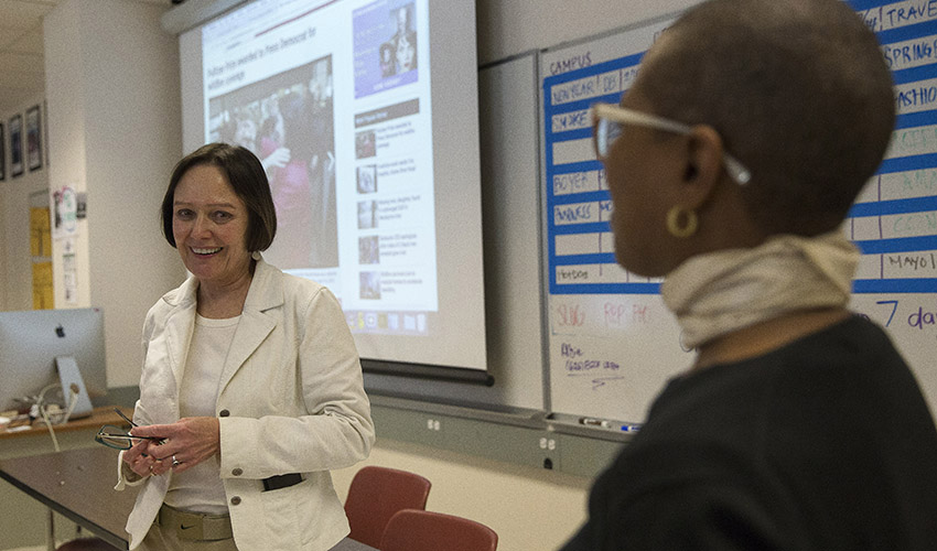 Joanne smiles and looks at Department Chair of Journalism Venise Wagner in a classroom