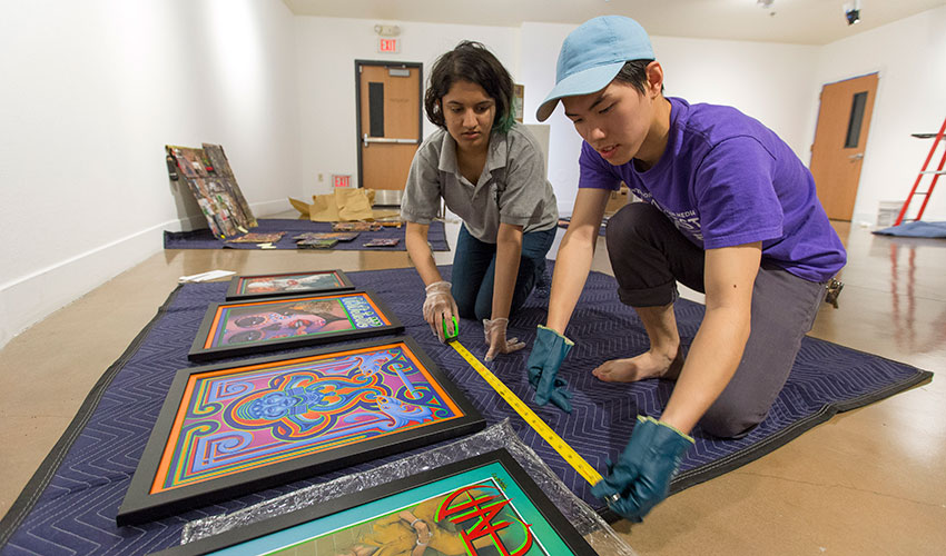 Two students handle paintings in an art gallery.