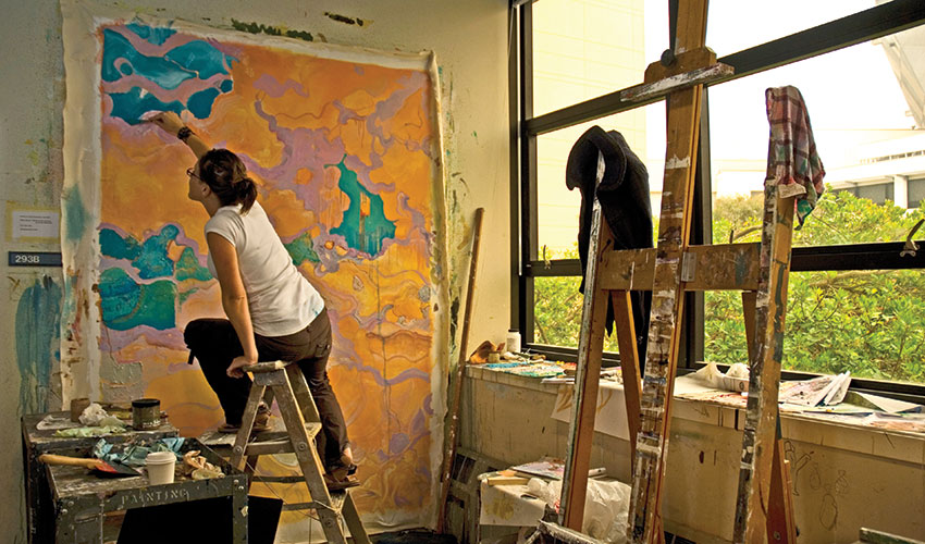 A woman sits on a ladder while working on a large orange painting.
