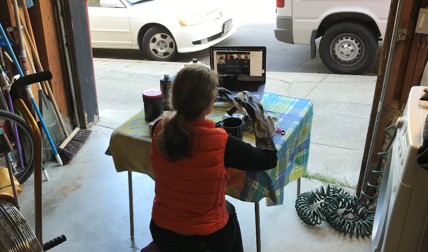 Woman in garage handles film canister, facing a laptop with a videoconferencing program open