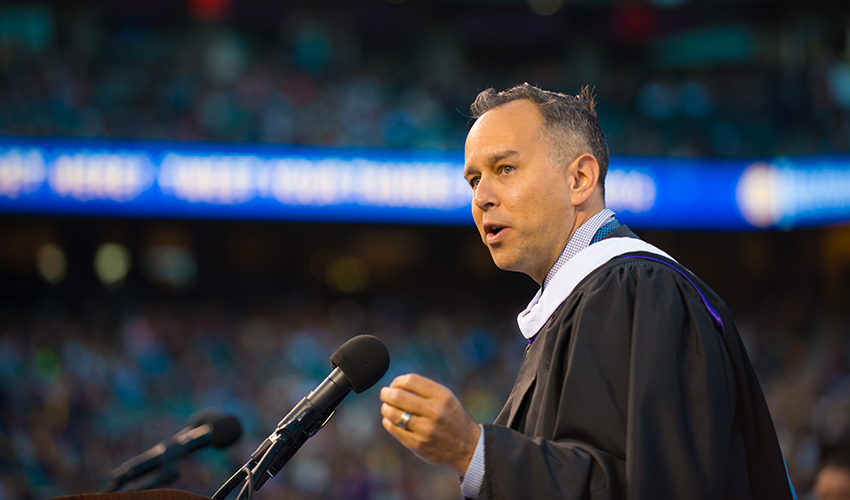 Jonas Rivera stands at a podium speaking in front of a crowd of graduates at AT&T Park