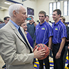Photo of alum Don Nasser holding a basketball, with student athletes