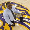 Athletic Director Charles Guthrie, with an SF State Gators shirt, kneeling on the gym center court logo