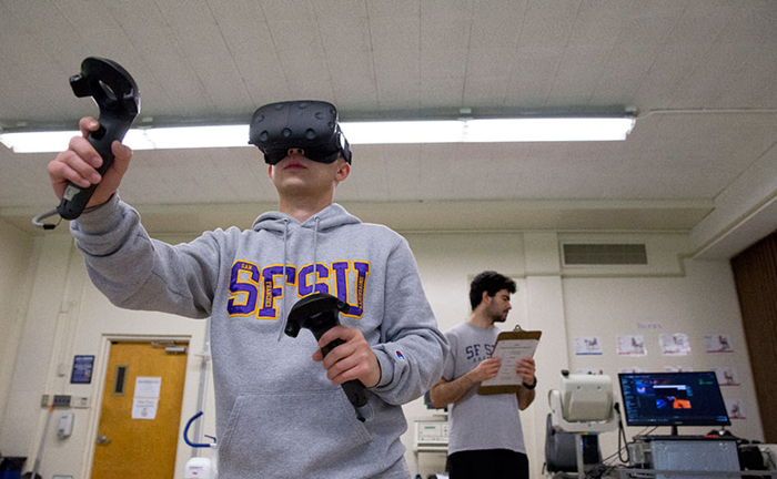A student subject wearing a headset plays a virtual reality game in the Department of Kinesiology's exercise lab while another student holds a clipboard and watches a computer monitor