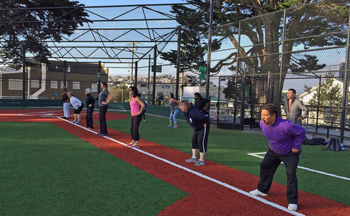 A group of people of varying ages work out at a park in San Francisco.